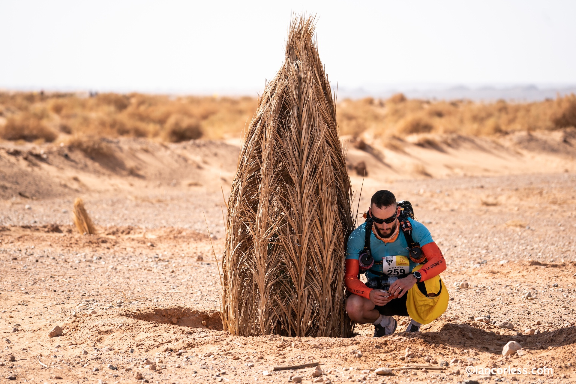 Runner seeking shade in Marathon des Sables
